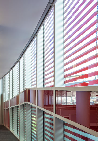 Interior architectural photography showing the coloured glass dado rail with patterned facade. 3 of 8