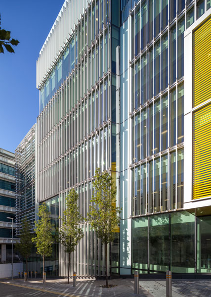 Photograph of an exterior view showing vertical solar shading and the entrance. 6 of 8