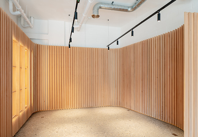 Interior spaces are divided by undulating timber partitions, 02 of 08.