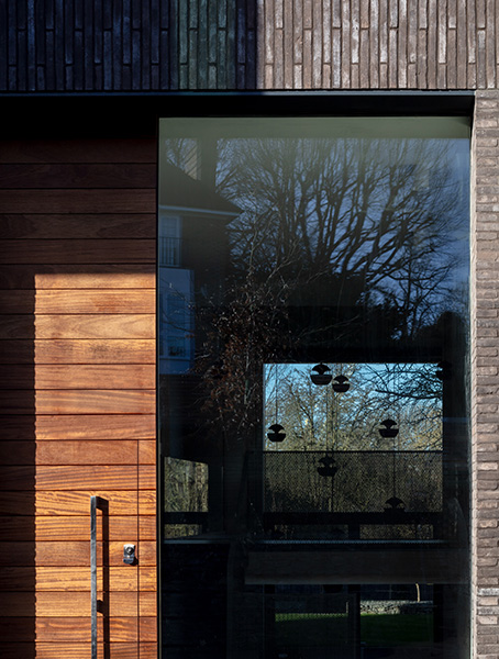 Entrance with timber door and large glazing creates connection to the garden beyond, 03 of 11.