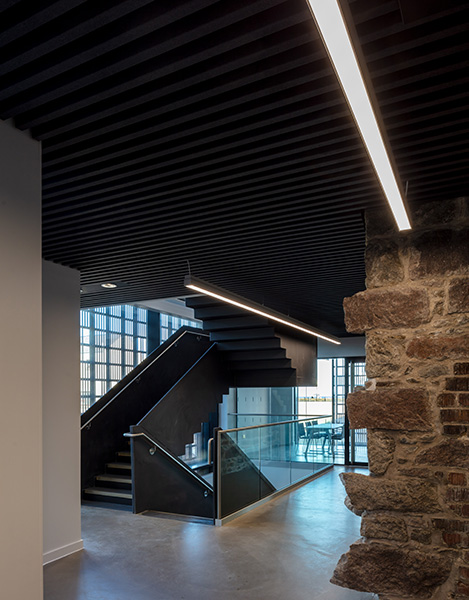 Interior photograph showing modern minimalist stair contrasting with existing roughly finished stone wall and black painted timber ceiling, 03 of 10.