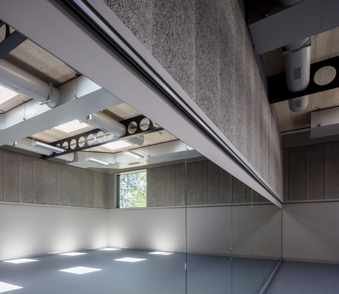 Interior photograph showing grey acoustic panelling and poured floor, 06 of 11.