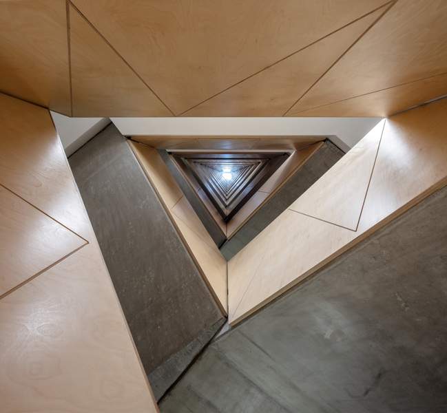 View up plywood-clad concrete stair to the rooflight, 15 of 18.