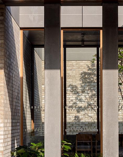 Hidden courtyard glimpsed through structural pre-cast concrete columns, 18 of 21.