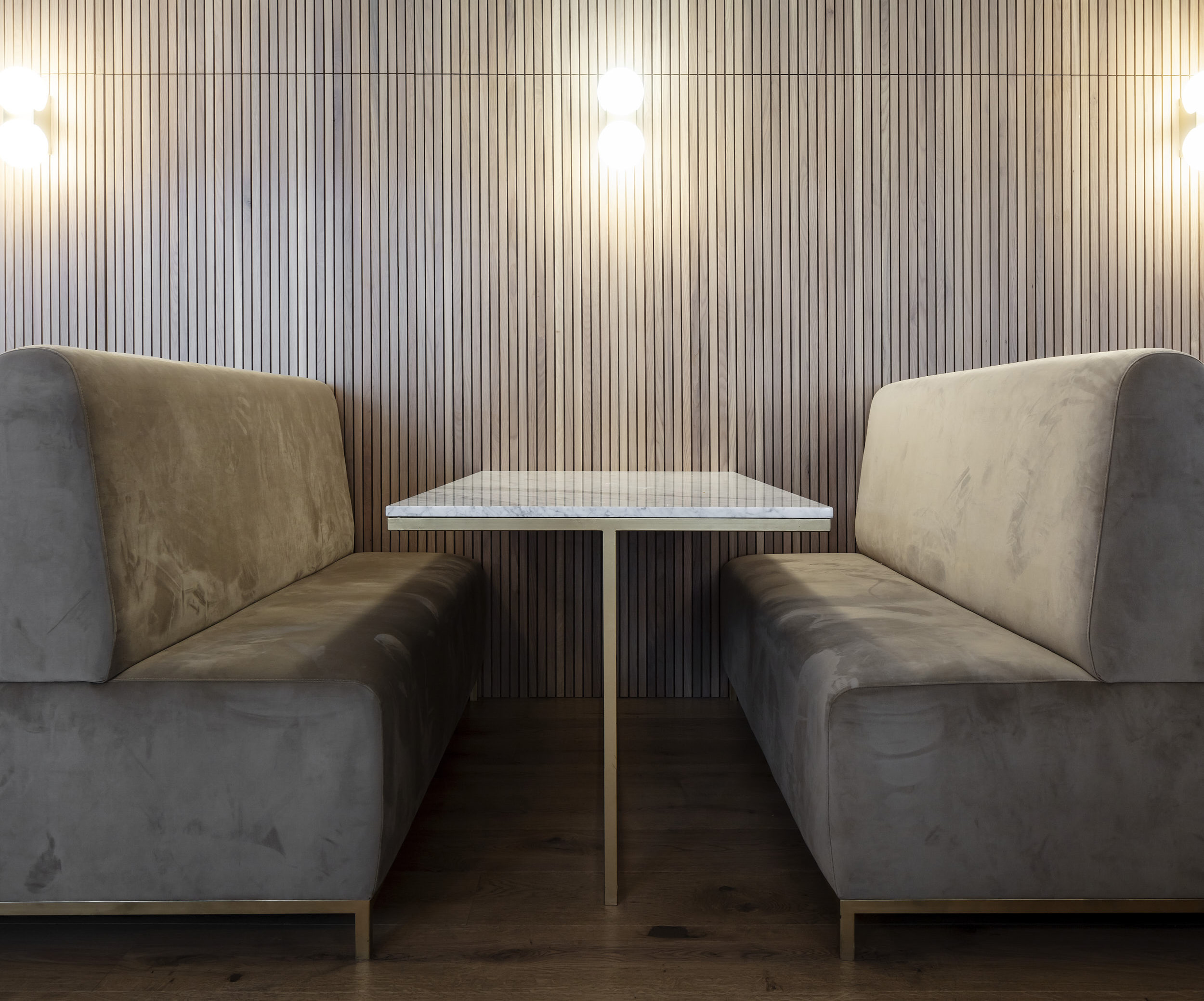 Banquette seating features custom furniture and timber wall-cladding.