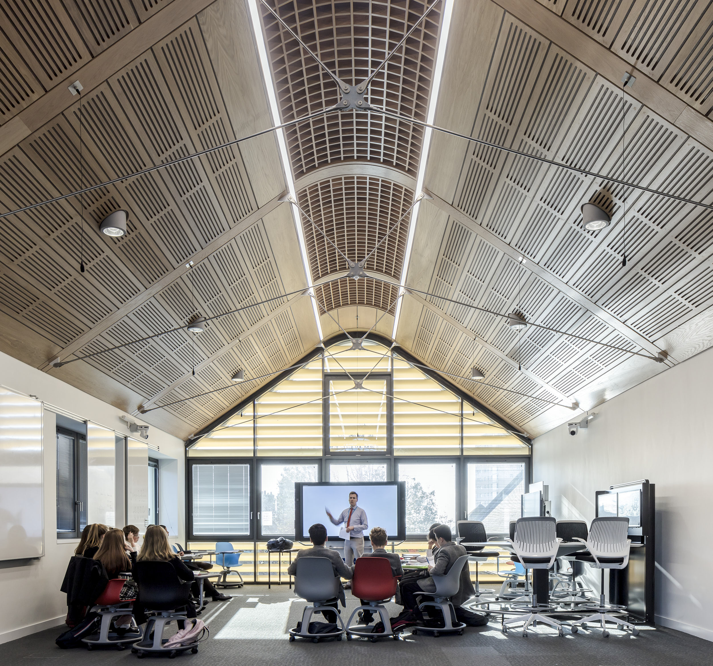 Interior photograph of a classroom featuring stunning, acoustically-panelled ceiling and visible structural bracing.