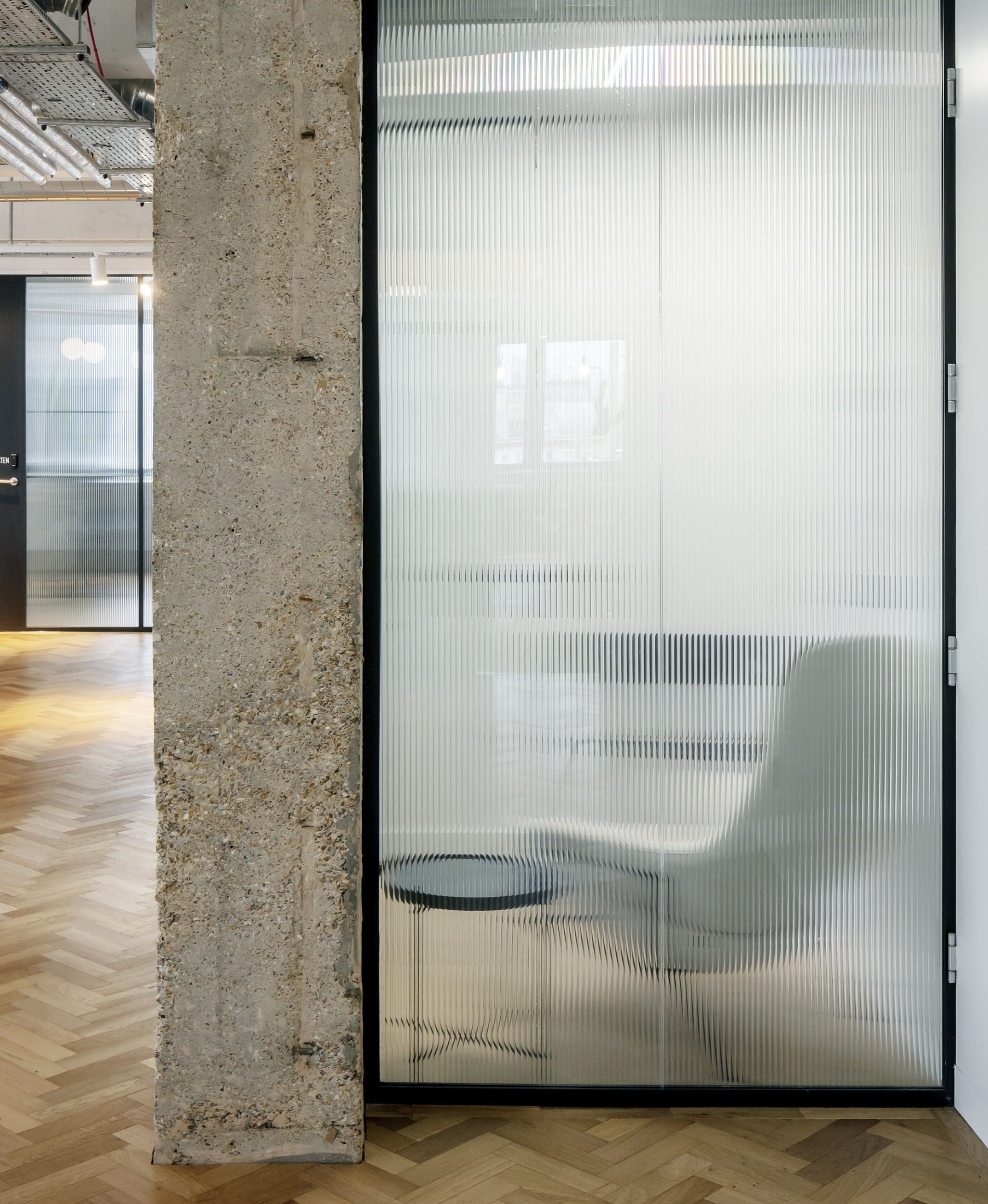 Interior photography showing fluted glass screens creating privacy while maintaining-connections and delivering light.