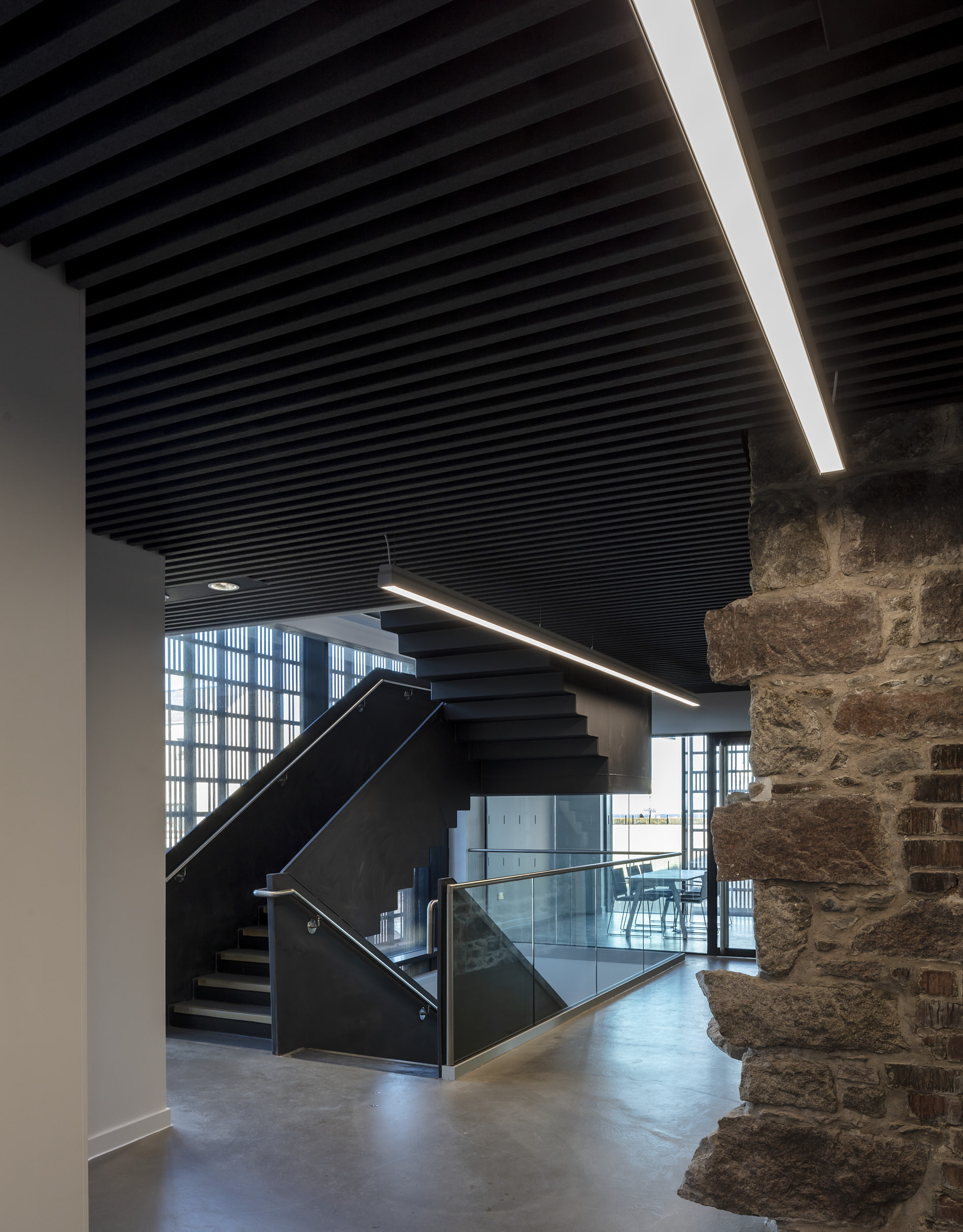 Interior photograph showing modern, minimalist stair contrasting with the existing, roughly-finished stone wall and black painted timber ceiling.