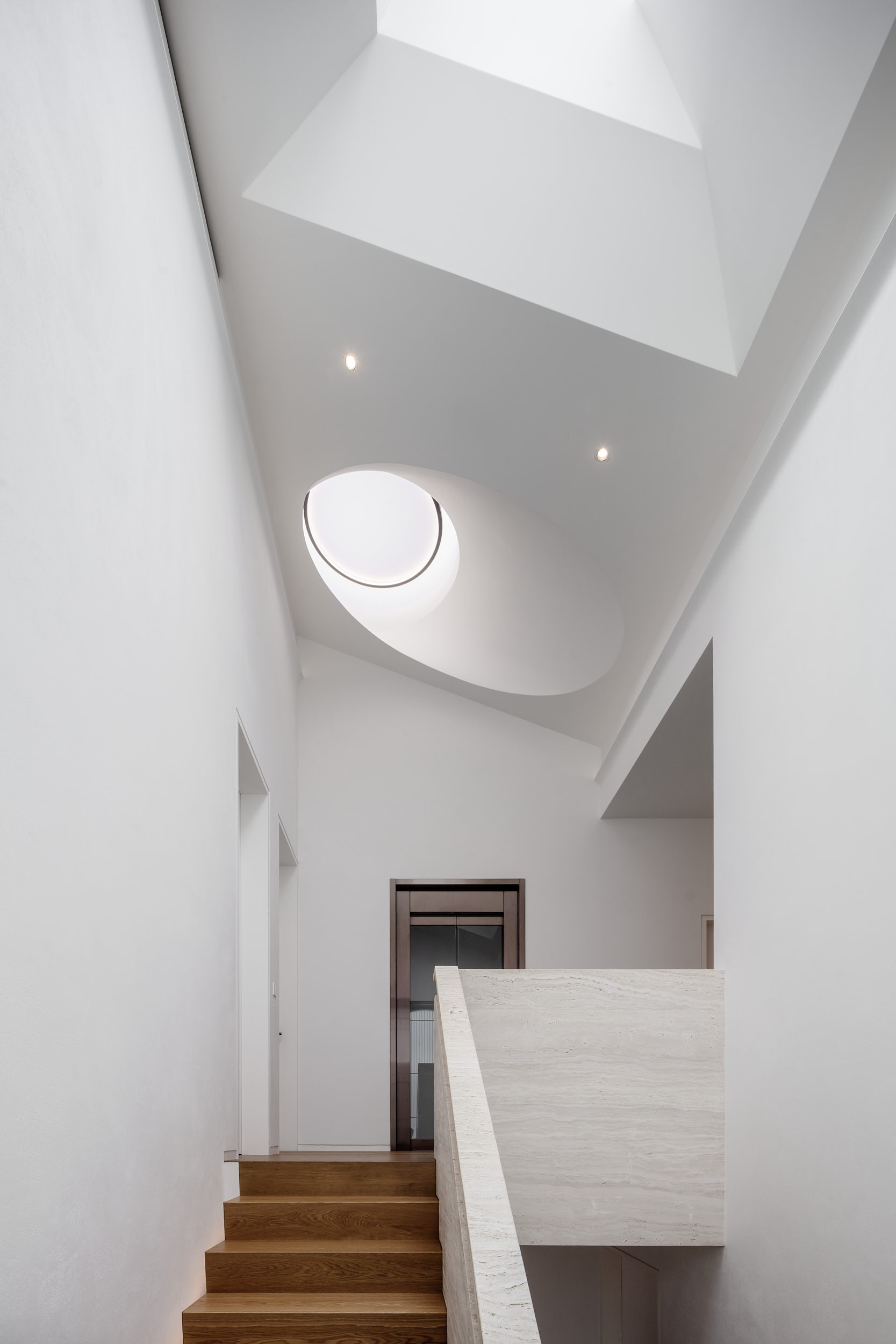 Sculptural rooflight at the top of the stairs floods the space with light.