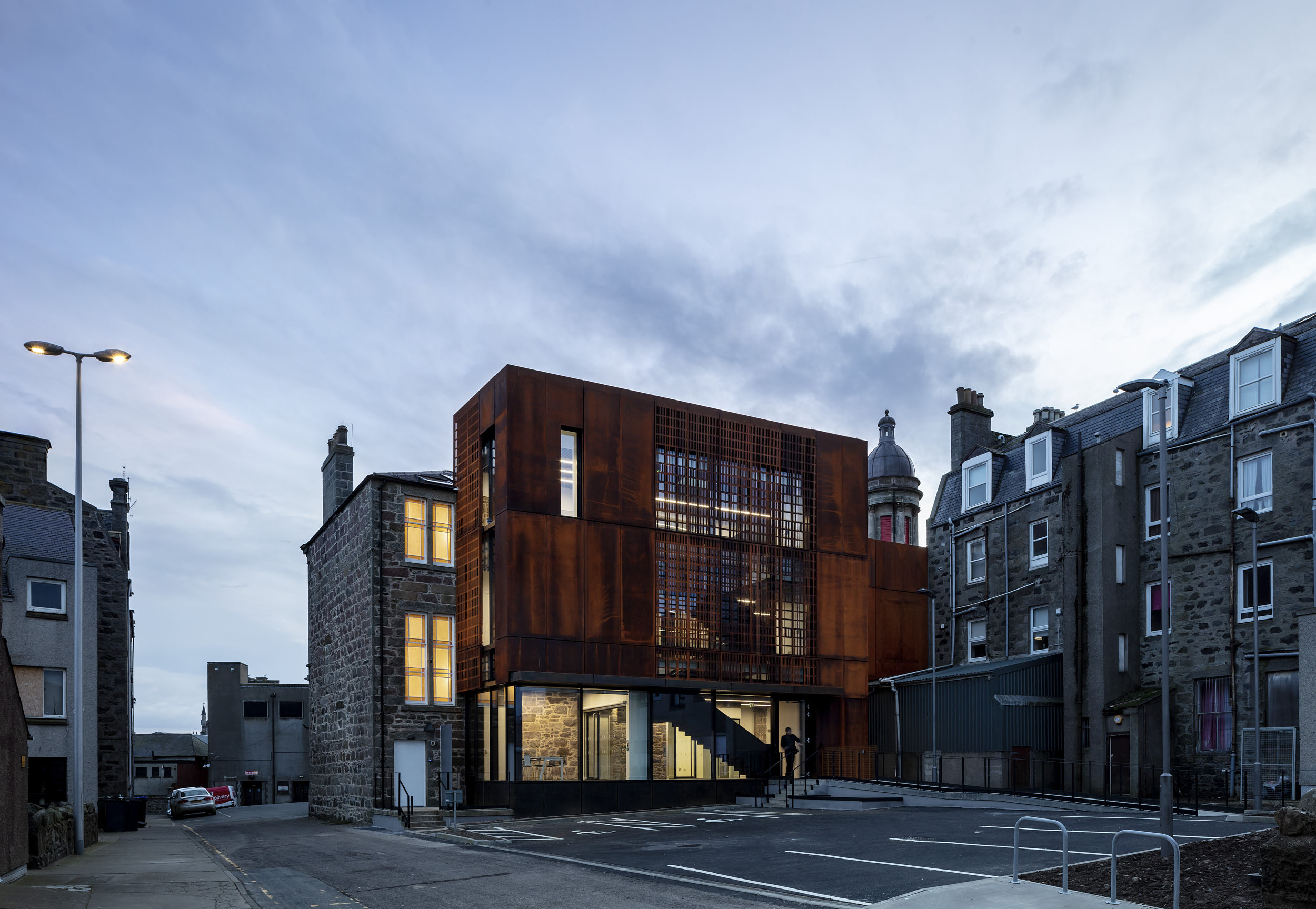 Exterior dusk photograph that shows the contrasting colours of the cor-ten steel in its traditional context.