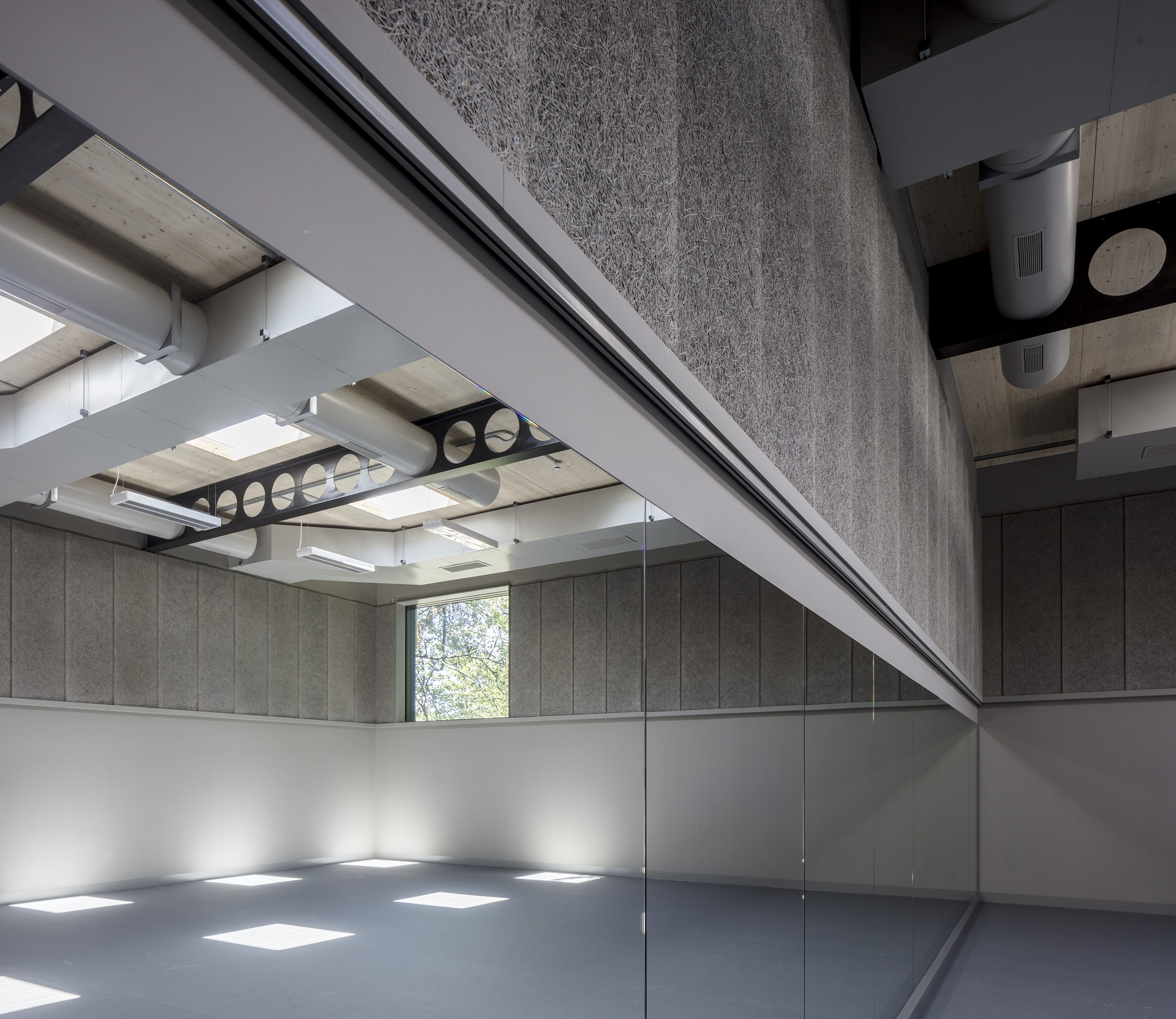 Rehearsal space features mirrors, rooflights and a controlled and subtle material palette.