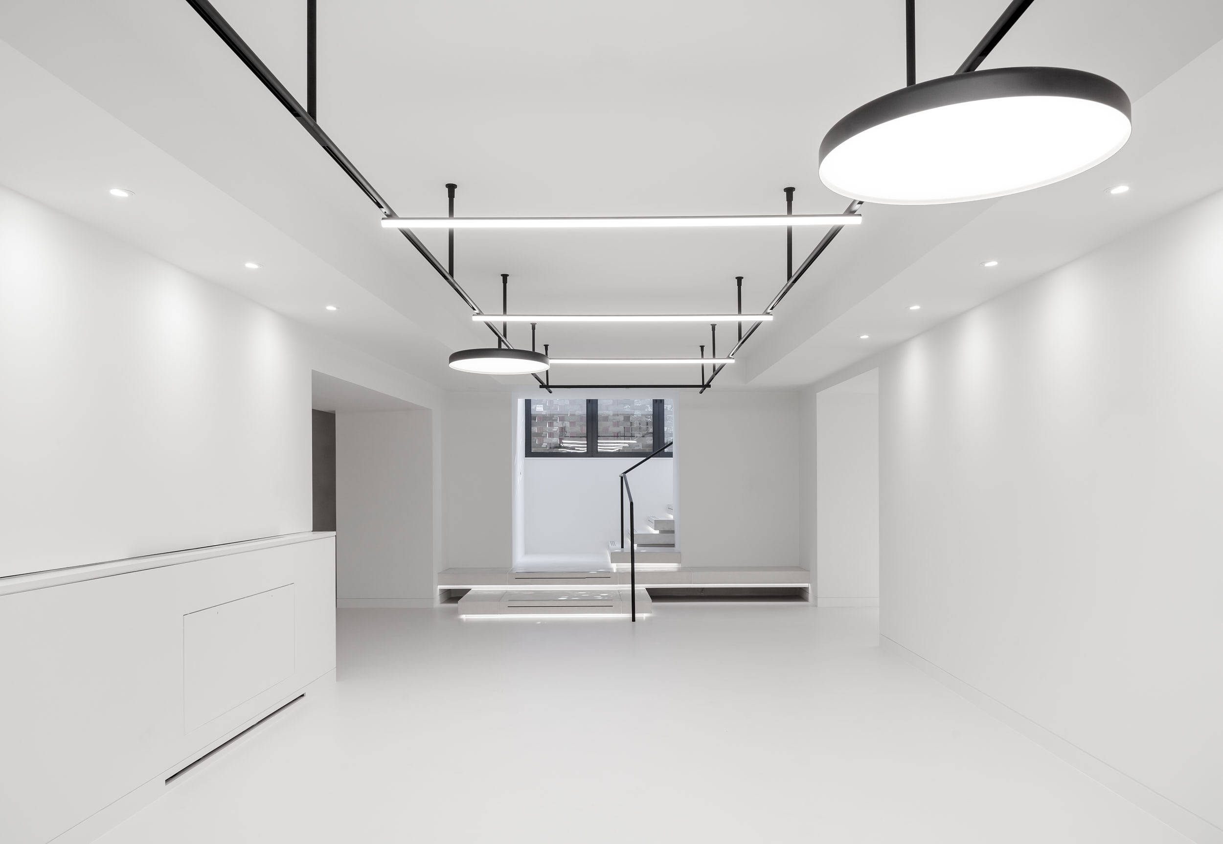 Interior design features custom black lighting track and bespoke joinery.