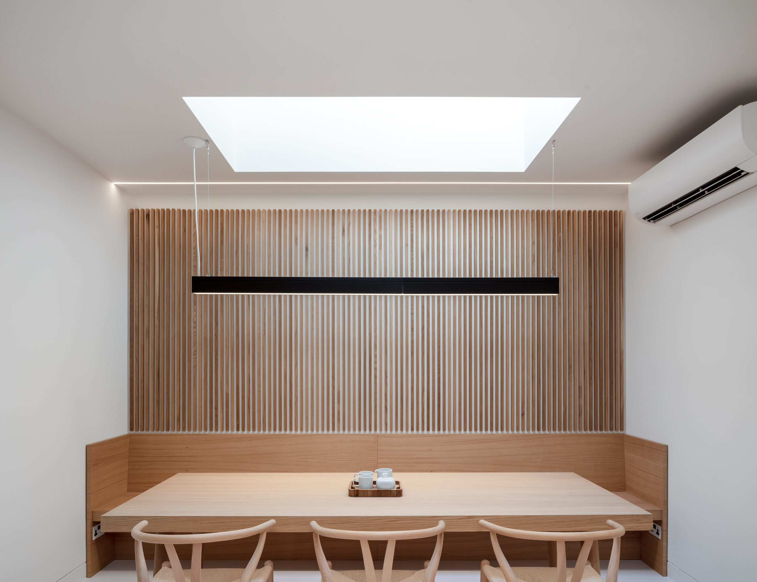 Dining and meeting area with timber panelling and classic, modernist furniture.