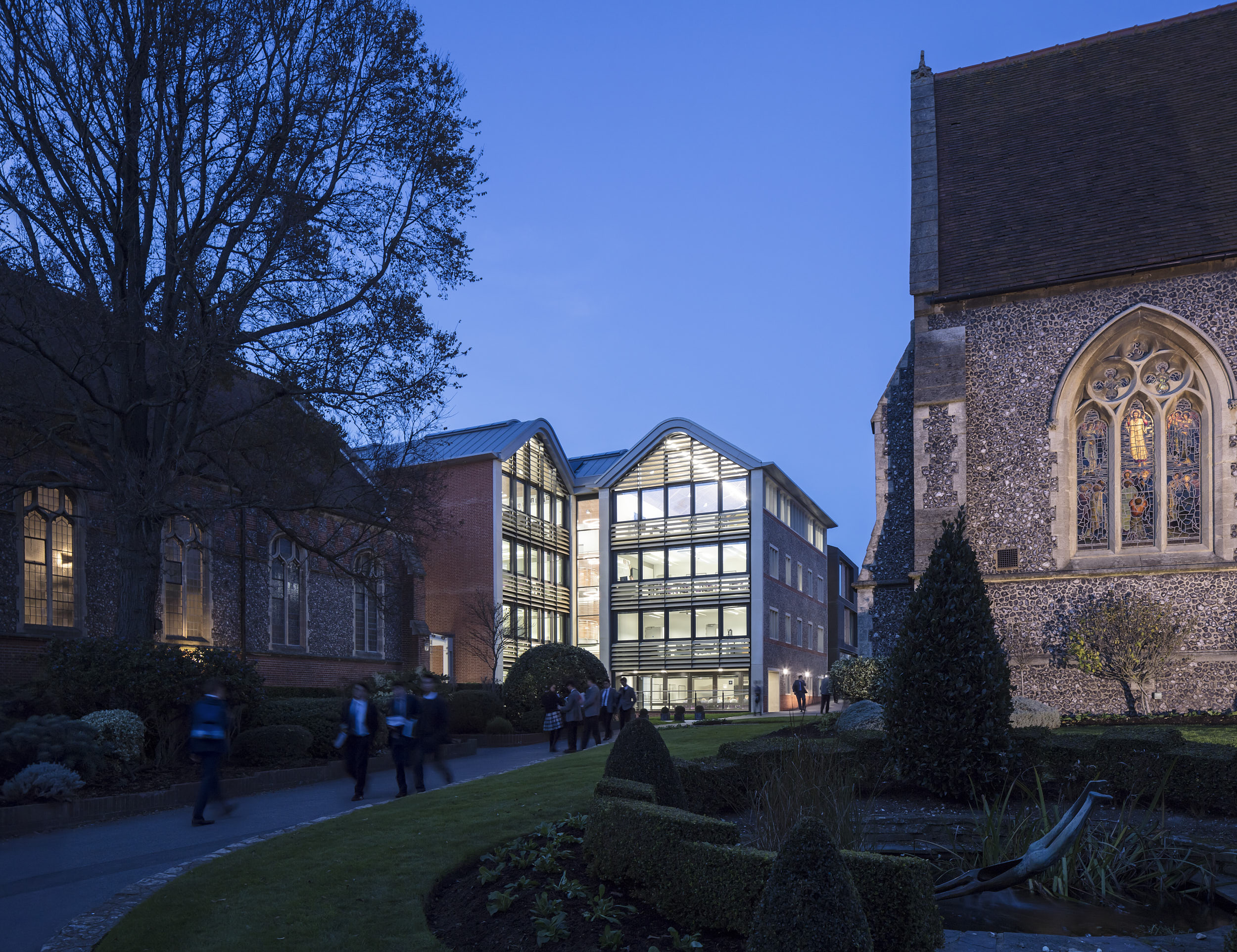 Exterior night view showing the new, glazed architecture in its historical context.