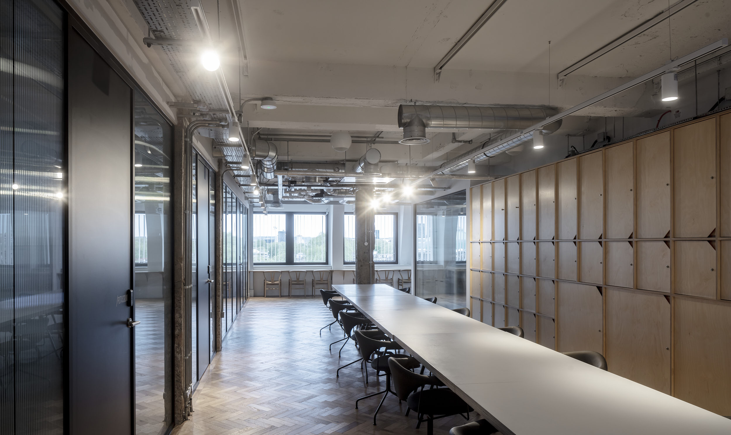 Long coworking tables and ply-faced cupboard doors.