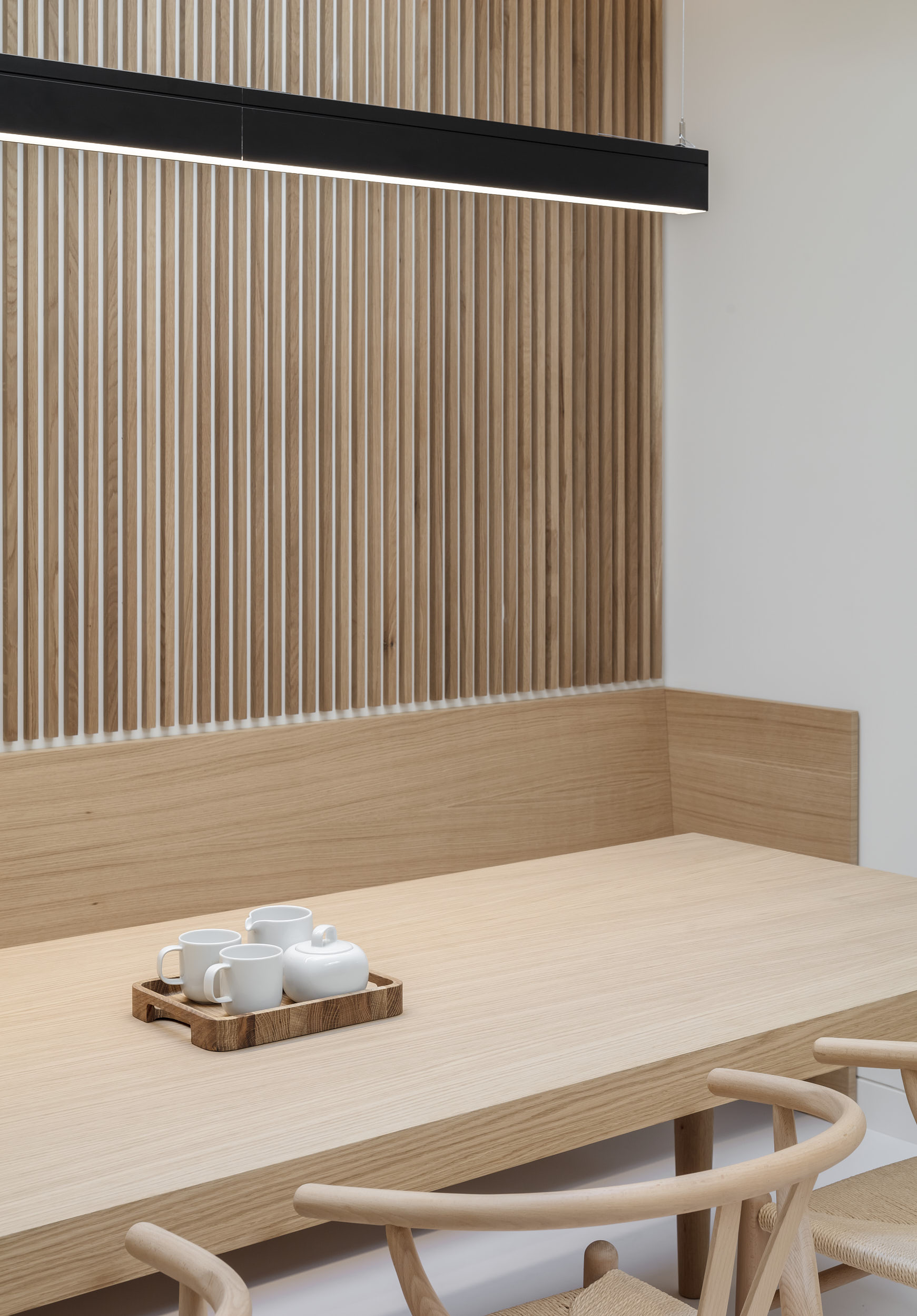 Minimalist dining and meeting space featuring bespoke furniture and timber cladding.