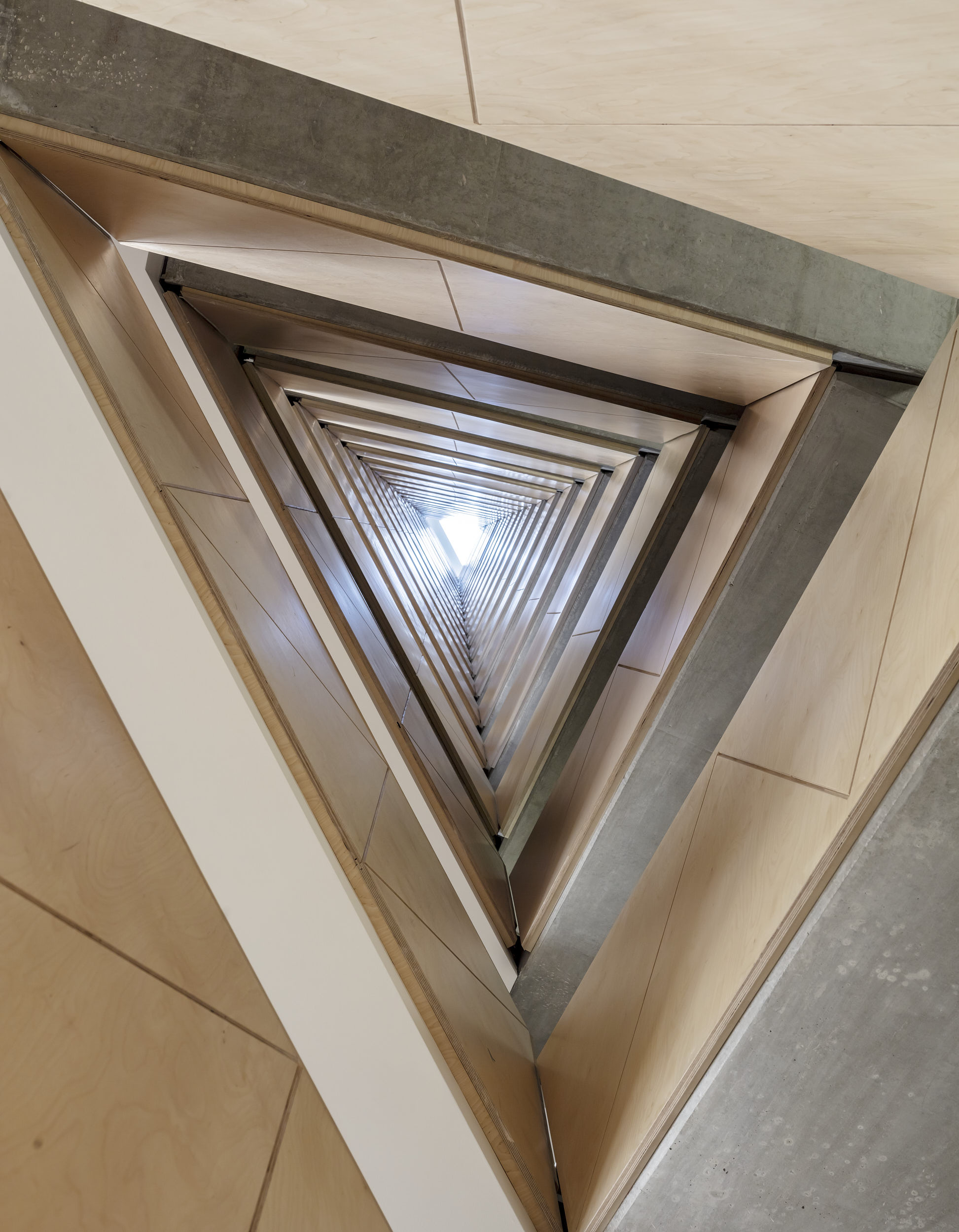 View up the plywood-clad concrete stair to the rooflight.