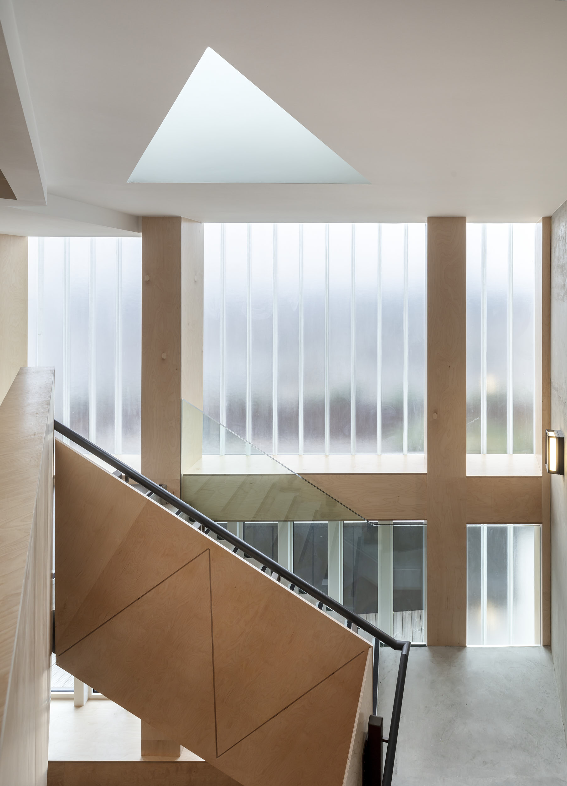 The space at the top of the stairs features glass planks and sculptural rooflights.