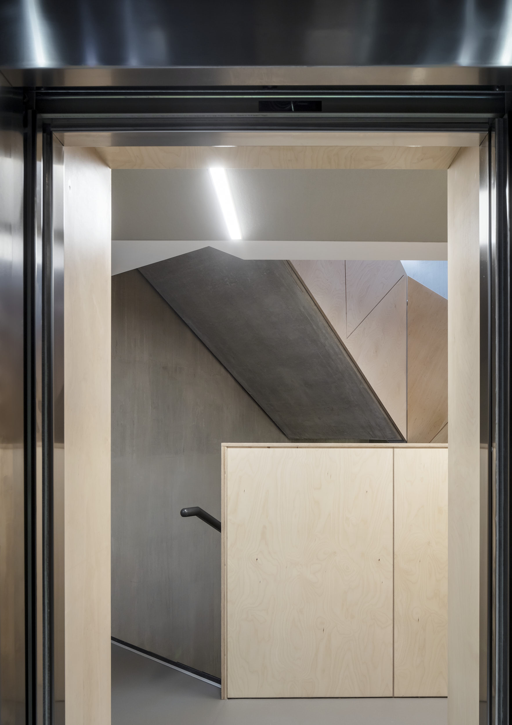 Interior view from the lift lobby showing the ply panelling and sculptural concrete stair.