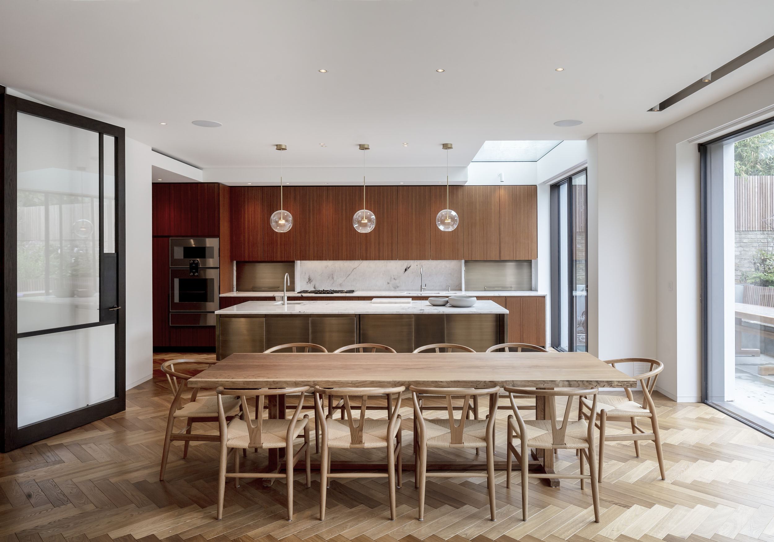 The stunning kitchen features bronze and veneer doors and classic modernist furniture.